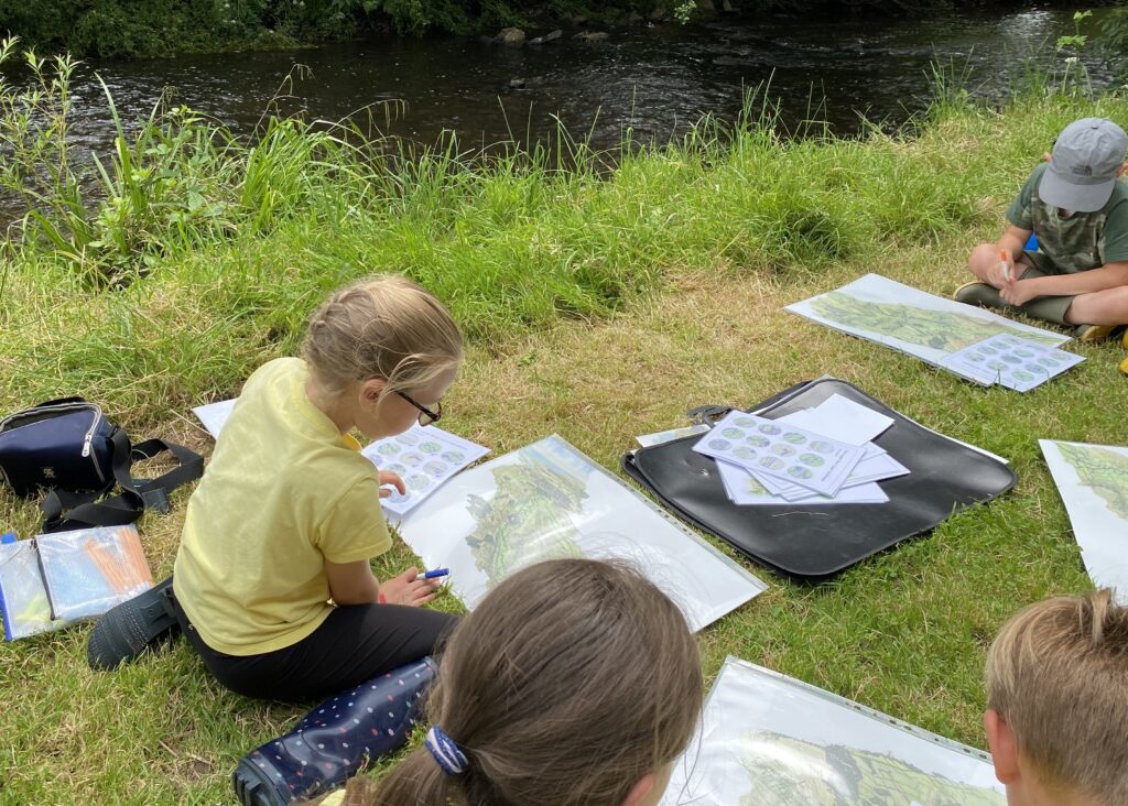 Children working with images of the river culm by the river