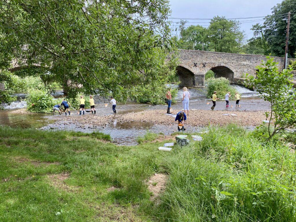 children play in river by bridge