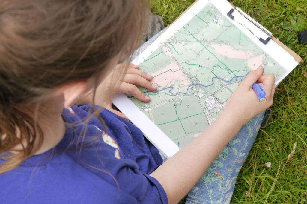 Child examining river landscape map
